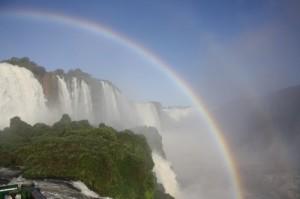 Um arco-íris bem no meio da tarde encanta os visitantes que apreciam as Cataratas